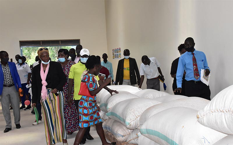 """The Government of Uganda through the National Agricultural Advisory Services (NAADS) in partnership with World Food Programme (WFP) handed over another modern community grain store to farmers in Kyegegwa district. The 300 MT store located in Katente Village in Kyegegwa Town council is one of the Government initiatives aimed at reducing post-harvest losses, promoting value addition and collective marketing systems, besides improving access to agro-inputs in selected parts of the country. Through these stores small hold farming communities are able to access formal markets through group bulking and marketing. The intervention is in line with government initiative to reduce pots-harvest losses and improve on the quality of grain produced in Uganda. Speaking to the farmers during the handover of the store, the Chairperson LC5 Kyegegwa district John Byamukama said the store is the first of its kind in Kyegegwa district where 95 percent of the people are farmers. He cautioned the farmers to desist from selling maize from the gardens to get quick money. """"If Kyegegwa is to get value for money from the store, all the grain farmers should use the store to bulk maize and ensure that they bring quality maize"""", said Byamukama. The Chairperson of the Kyegegwa Farmers Association thanked NAADS and WFP for the support and said that since the store opened in 2020, farmers started bulking their maize and the quality of their maize has greatly improved overtime. The farmers asked Government for more support in form of a maize mill to add value to their maize and tap into the available market in Kyaka refugee camp which is located within the district. The Manager Technical and Agribusiness Services who represented the Executive Director NAADS Dr. Christopher Bukenya said NAADS will continue to work with other partners to address the challenges still faced by the farmers especially the maize mill which farmers said its urgently needed. Dr. Bukenya implored the leaders to mobilize more f"""